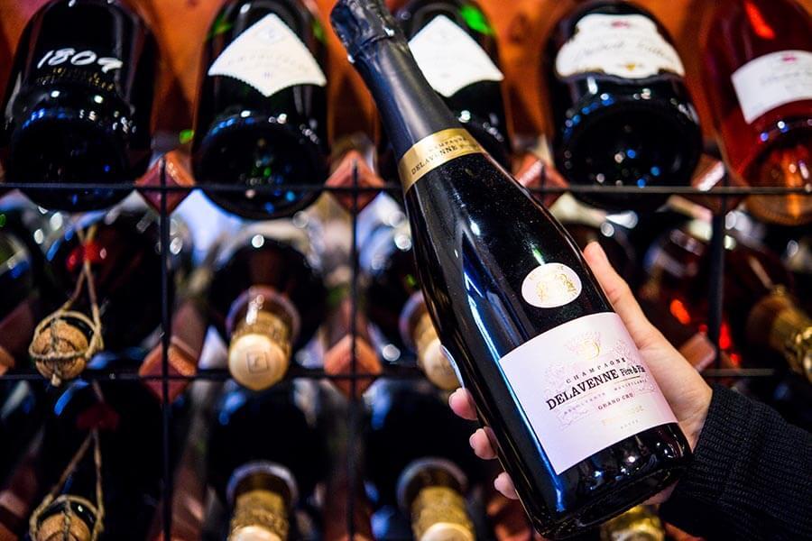 hand holding wine bottle in front of wine racks full of wine